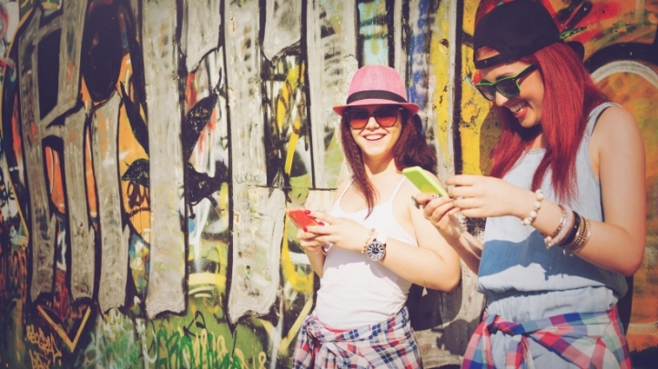 millennials-teenagers-girls-smartphones-texting-women-graffiti-wall-friends-hipsters-happy-young