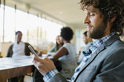 Businessman checking phone for messages during meeting
