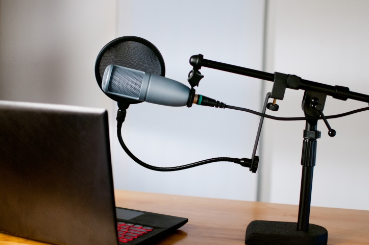 Studio microphone and a laptop sit on a desk