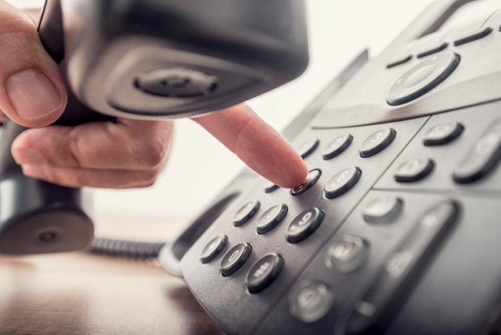 Closeup of male hand holding telephone receiver while dialing a